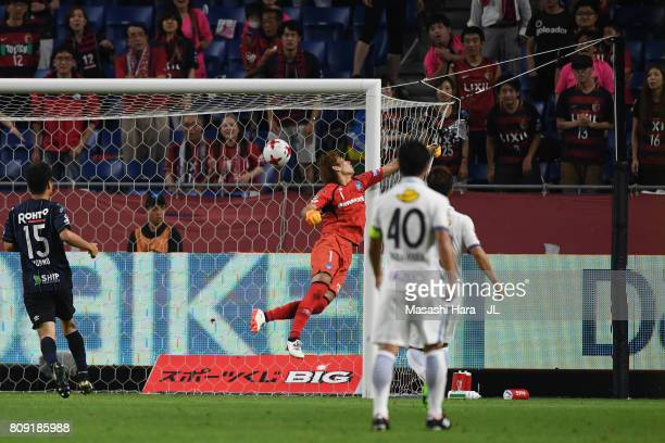 Masaaki Higashiguchi of Gamba Osaka dives in vain as Yasushi Endo of Kashima Antlers scores the opening goal during the JLeague J1 match between...