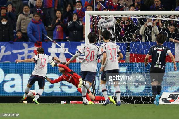 Masaaki Higashiguchi of Gamba Osaka saves a shot by Yoshito Okubo of FC Tokyo during the JLeague J1 match between Gamba Osaka and FC Tokyo at Suita...