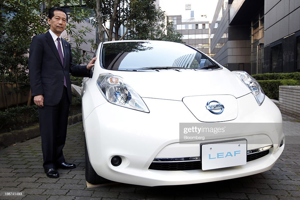 Masaaki Nishizawa, senior vice president of Nissan Motor Co., stands alongside the updated Nissan Leaf electric vehicle (EV) during a news conference in Tokyo, Japan, on Tuesday, Nov. 20, 2012. Nissan Motor Co., Japan's second-largest carmaker, introduced a cheaper version of the Leaf electric vehicle to lure cost-conscious buyers as sales of the original model lag behind the company's target. Photographer: Kiyoshi Ota/Bloomberg via Getty Images
