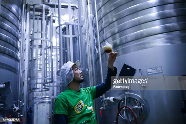 Masafumi Morita brewing director at YoHo Brewing Co inspects the condition of a brew from a fermentation tank at the company's brewery in Saku Nagano...
