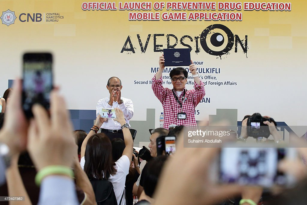 Masagos Zulkilfi (L), Second Minister for Home Affairs and Second Minister for Foreign Affairs introduces Hong actor and director, Jackie Chan as Singapore's first celebrity anti-drug ambassador during the launch of a new mobile anti-drug game application, Aversion at Nanyang Polytechnic on May 7, 2015 in Singapore.