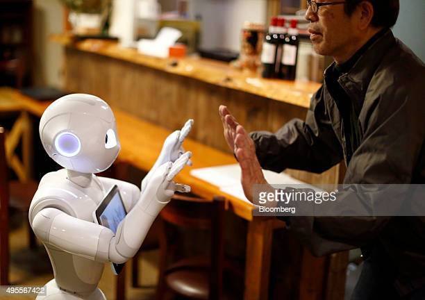 Masahiko Yoshida owner of a karaoke bar reaches to touch hands with Pepper the humanoid robot manufactured by SoftBank Group Corp at his bar in...