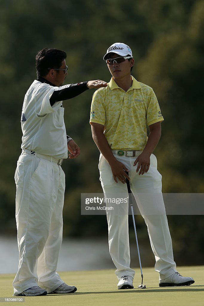 Masahiro Kawamura of Japan discusses his putt with his caddie on the 18th green during day three of the Panasonic Japan Open at Ibaraki Golf Club on September 28, 2013 in Ibaraki, Japan.