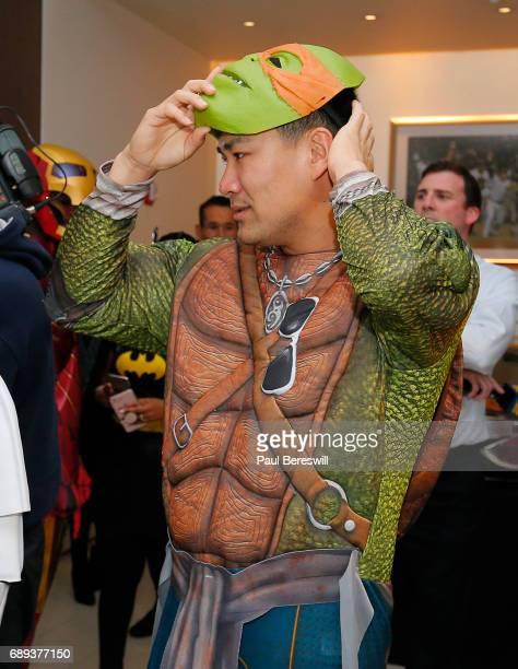 Masahiro Tanaka of the New York Yankees adjusts his mask as he is dressed as Teenage Mutant Ninja Turtle Michelangelo at a Yankees pregame Hope Week...