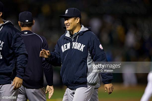Masahiro Tanaka of the New York Yankees celebrates with teammates after the game against the Oakland Athletics at Oco Coliseum on May 30 2015 in...