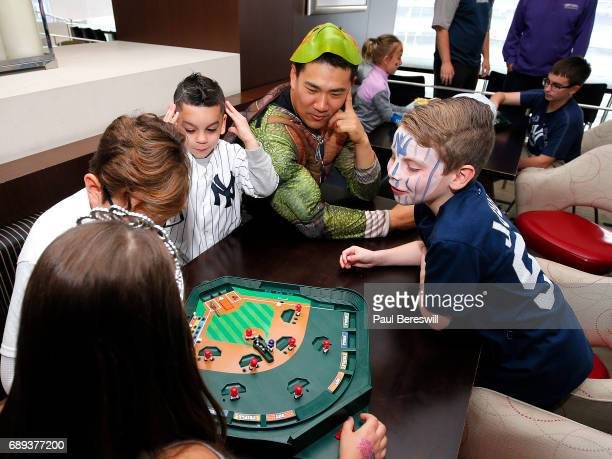 Masahiro Tanaka of the New York Yankees is dressed as Teenage Mutant Ninja Turtle Michelangelo as he watches children play a tabletop baseball game...