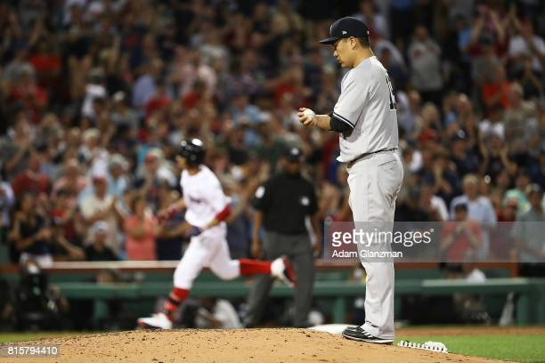 Masahiro Tanaka of the New York Yankees looks on as Mookie Betts of the Boston Red Sox rounds the bases after hitting a tworun home run in the third...