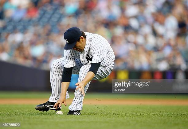 Masahiro Tanaka of the New York Yankees makes a play to throw out Melky Cabrera of the Toronto Blue Jays in the first inning during their game at...