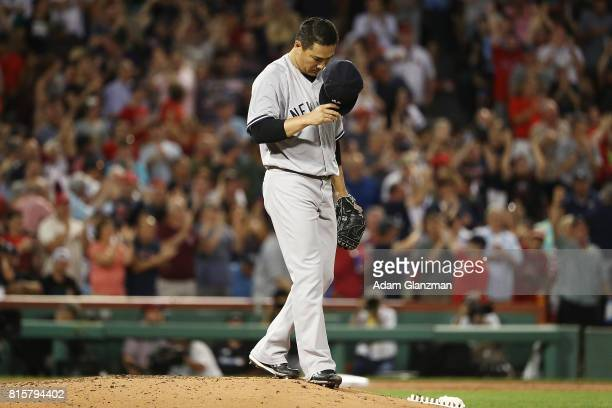 Masahiro Tanaka of the New York Yankees reacts after giving up a tworun home run to Mookie Betts of the Boston Red Sox in the third inning during...