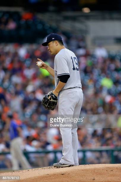 Masahiro Tanaka of the New York Yankees signals to the catcher before tossing a warmup pitch during the first inning of a game against the Detroit...