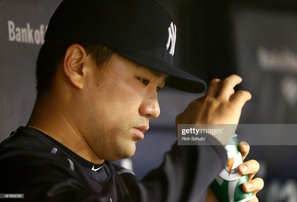 Masahiro Tanaka #19 of the New York Yankees sits with a drink in the dugout during the seventh inning during a MLB baseball game against the Toronto Blue Jays at Yankee Stadium on September 11, 2015 in the Bronx borough of New York City.