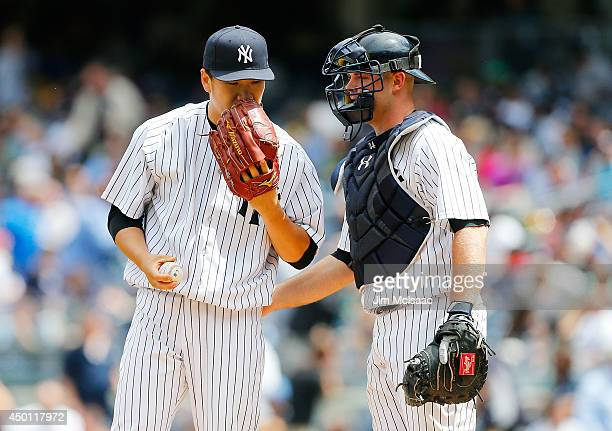 Masahiro Tanaka of the New York Yankees talks with teammate Brian McCann during the fourth inning against the Oakland Athletics at Yankee Stadium on...