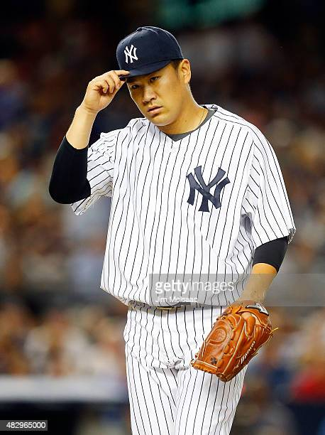 Masahiro Tanaka of the New York Yankees walks to the dugout after the fifth inning against the Boston Red Sox at Yankee Stadium on August 4 2015 in...