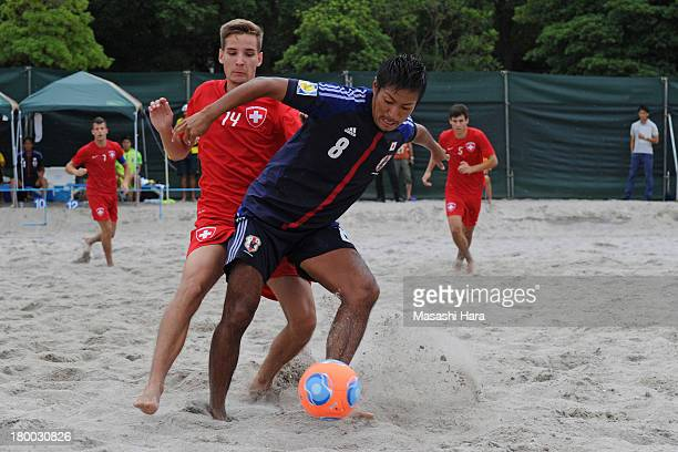 Masahito Toma of Japan and Remo Wittlin of Switzerland compete for the ball during the beach soccer international friendly between Japan and...