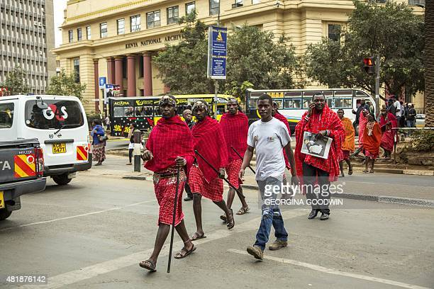 Masai men in traditional attire walk across the street on July 25 on their way to their traditional dance performance at the Kenyatta International...
