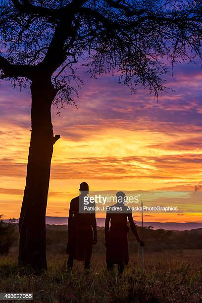 Masai tribesmen by acacia tree at sunrise