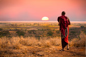 Masai man, wearing traditional blankets, overlooks Serengeti in Tanzania as the colorful sunset fills the sky.  Wild grass in the forground.