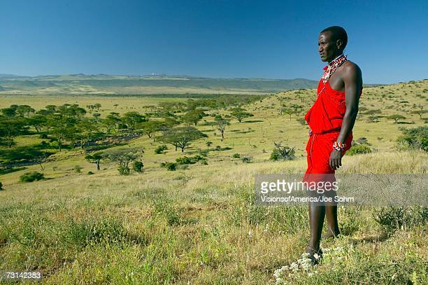 Masai Warrior in red surveying landscape of Lewa Conservancy, Kenya, Africa