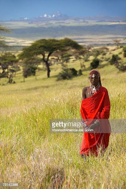 Masai Warrior in red surveying landscape of Lewa Conservancy, Kenya Africa