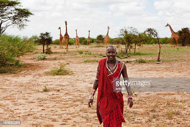 Masai warrior on the savannah with giraffes in background.