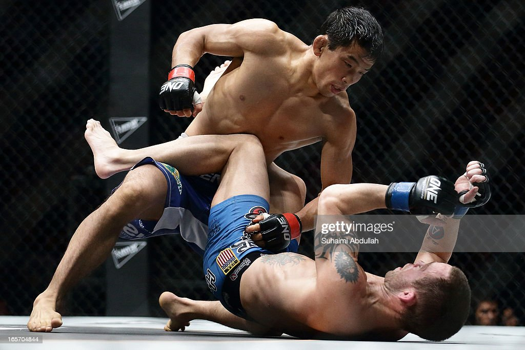 Masakatsu Ueda of Japan (top) grounds and pounds Jens Pulver of United States of America during the One Fighting Championship at Singapore Indoor Stadium on April 5, 2013 in Singapore.