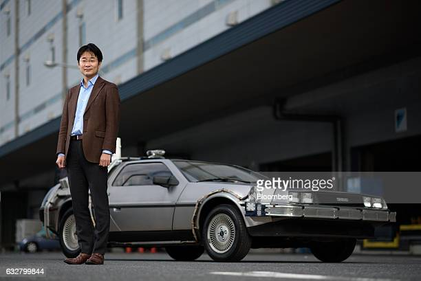 Masaki Takao cofounder and chief executive officer of Jeplan Inc poses for a photograph with a replica of the timetraveling DeLorean featured in the...