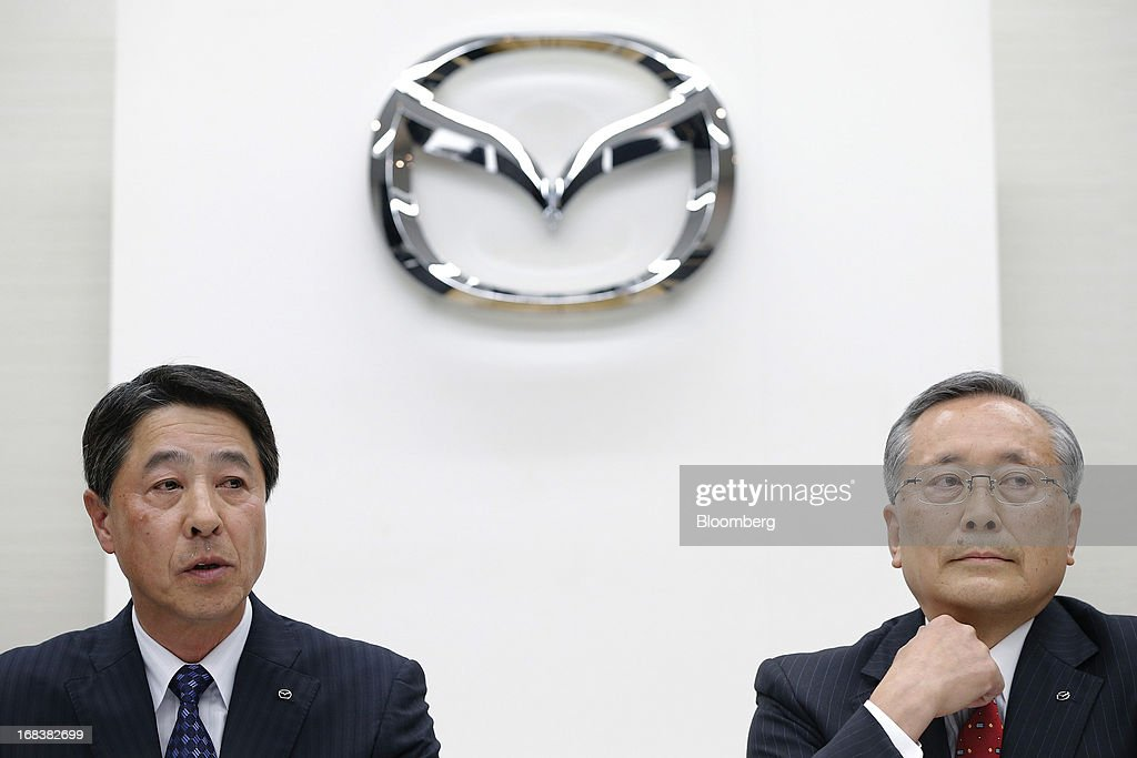 Masamichi Kogai, incoming president and chief executive officer of Mazda Motor Corp., left, speaks while <a gi-track='captionPersonalityLinkClicked' href=/galleries/search?phrase=Takashi+Yamanouchi&family=editorial&specificpeople=5292471 ng-click='$event.stopPropagation()'>Takashi Yamanouchi</a>, incoming chairman of Mazda Motor Corp., listens during a news conference in Tokyo, Japan, on Thursday, May 9, 2013. Mazda, Japan's most export-dependent carmaker, said <a gi-track='captionPersonalityLinkClicked' href=/galleries/search?phrase=Takashi+Yamanouchi&family=editorial&specificpeople=5292471 ng-click='$event.stopPropagation()'>Takashi Yamanouchi</a> will step down as president next month to make way for younger managers after the company returned to profitability. Photographer: Kiyoshi Ota/Bloomberg via Getty Images