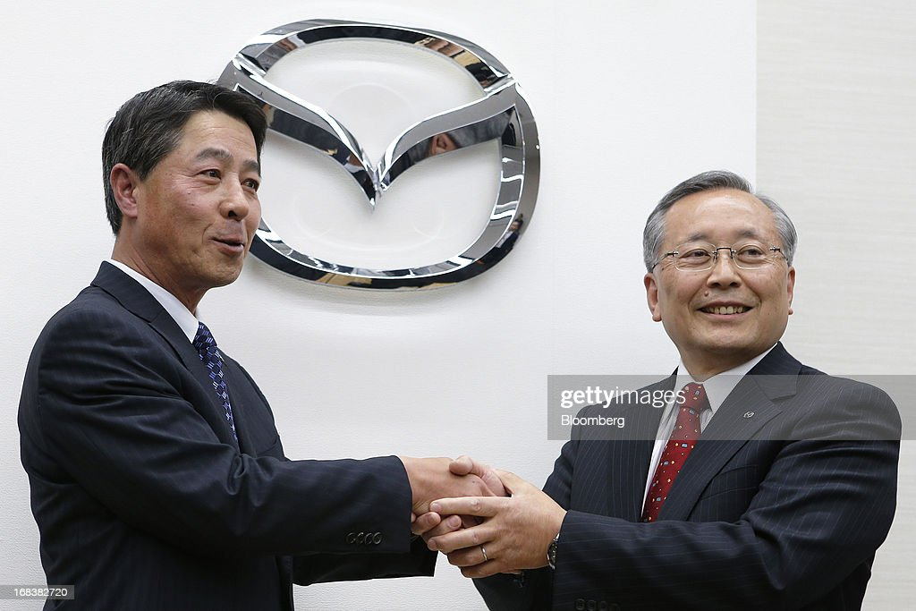 Masamichi Kogai, incoming president and chief executive officer of Mazda Motor Corp., left, shakes hands with <a gi-track='captionPersonalityLinkClicked' href=/galleries/search?phrase=Takashi+Yamanouchi&family=editorial&specificpeople=5292471 ng-click='$event.stopPropagation()'>Takashi Yamanouchi</a>, incoming chairman of Mazda Motor Corp., during a news conference in Tokyo, Japan, on Thursday, May 9, 2013. Mazda, Japan's most export-dependent carmaker, said <a gi-track='captionPersonalityLinkClicked' href=/galleries/search?phrase=Takashi+Yamanouchi&family=editorial&specificpeople=5292471 ng-click='$event.stopPropagation()'>Takashi Yamanouchi</a> will step down as president next month to make way for younger managers after the company returned to profitability. Photographer: Kiyoshi Ota/Bloomberg via Getty Images