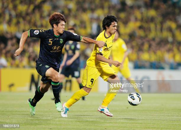 Masato Kudo of Kashiwa is challenged by Jung Inwan of Jeonbuk during the AFC Champions League round of 16 match between Kashiwa Reysol and Jeonbuk...