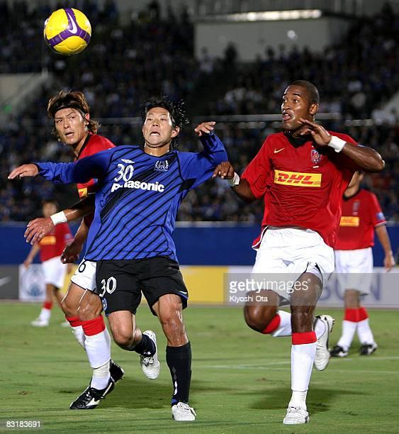 Masato Yamazaki of Gamba Osaka competes for the ball with Edmilson Dos Santos Silva and Takahito Soma of Urawa Red Diamonds during the AFC Champions...