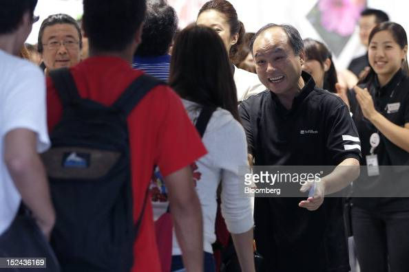 Masayoshi Son chairman and chief executive officer of SoftBank Corp welcomes customers during the launch of the Apple Inc iPhone 5 at SoftBank's...