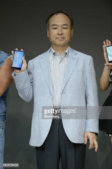 Masayoshi Son chairman and chief executive officer of SoftBank Corp poses for a photograph with the company's new Aquos Xx302SH smartphone during a...
