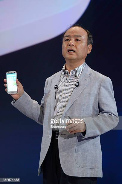 Masayoshi Son chairman and chief executive officer of SoftBank Corp introduces the company's Aquos Xx 302SH smartphone manufactured by Sharp Corp...