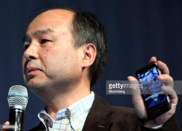 Masayoshi Son president and chief executive officer of SoftBank Corp holds the company's HTC Desire smartphone during the unveiling in Tokyo Japan on...