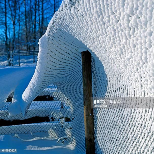 Maschendrahtzaun im laendlichen Garten biegt sich unter der Schneelast