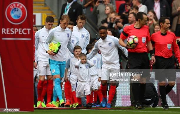 Mascot Bradley Lowery covers his ears as he walks out with Jermain Defoe of England during the FIFA 2018 World Cup Qualifier between England and...