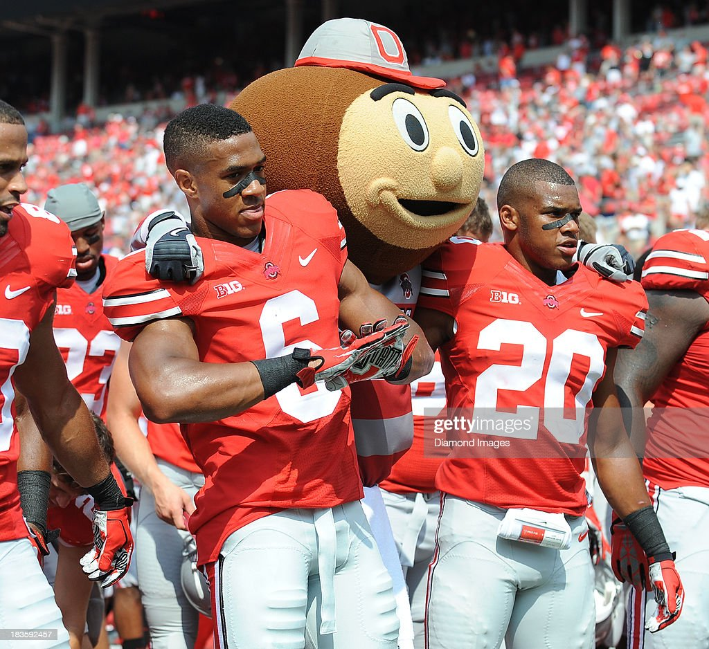 Mascot Brutus the Buckeye receiver Evan Spencer #6 and defensive back Ron Tanner sing 'Carmen Ohio' after a game against the Buffalo Bulls at Ohio Stadium in Columbus, Ohio. The Ohio State Buckeyes won 40-20.