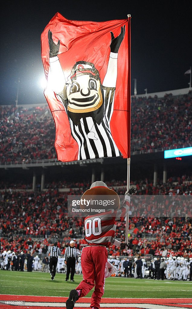 Mascot Brutus the Buckeye runs on the field with a flag after a Ohio State touchdown during a game between the Ohio State Buckeyes and the Penn State Nittany Lions at Ohio Stadium in Columbus, Ohio. The Buckeyes won 63-14.