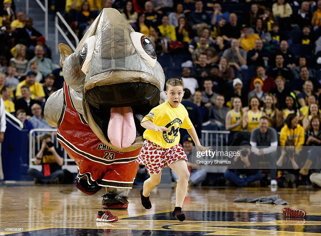 A mascot chases a youngster after swallowing him, spitting out his shoes and pants then him, during a game between the Holy Cross Crusaders and the Michigan Wolverines at Crisler Center on December 28, 2013 in Ann Arbor, Michigan. Michigan won the game 88-66.