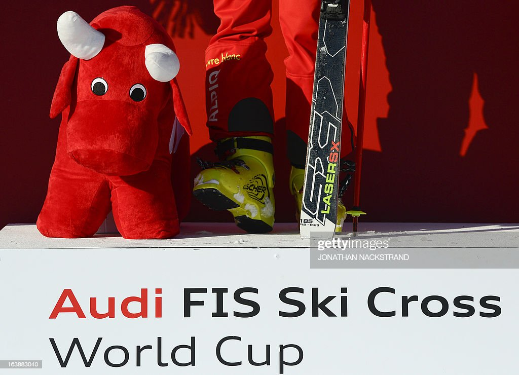 A mascot stands next to Switzerland's Fanny Smith on the podium as she won the final of the ladies' Audi FIS World Cup Ski Cross event in Are, Sweden, on March 17, 2013. Switzerland's Fanny Smith placed first.