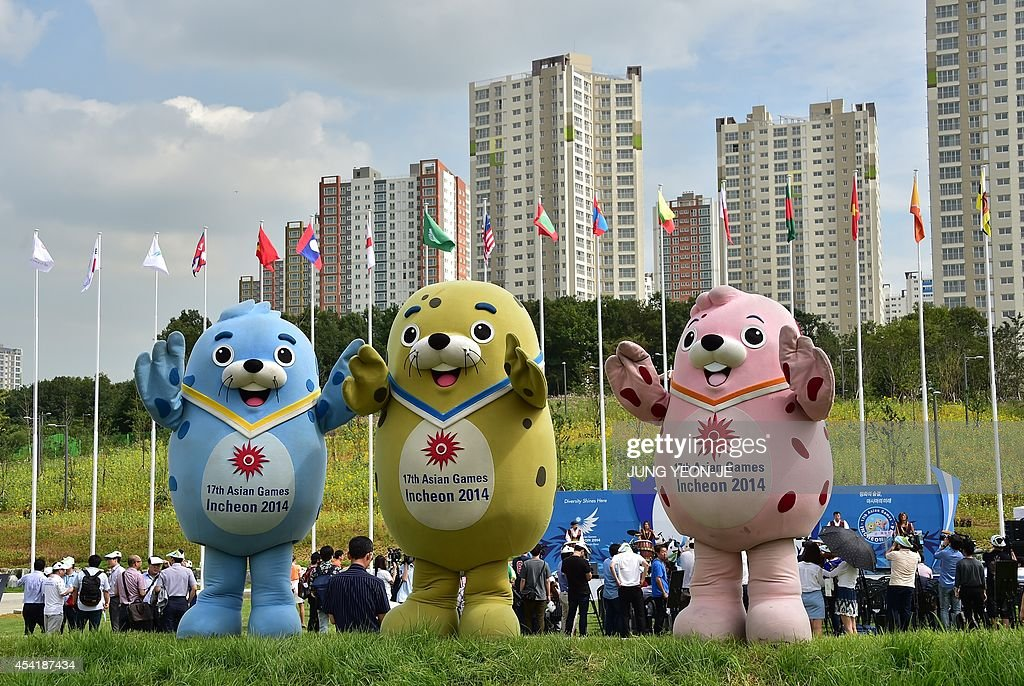 Mascots named Barame Vichuon and Chumuro pose on the flag plaza of the Athletes' Village for the upcoming 2014 Asian Games during a media tour in...