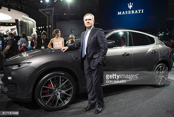 Maserati CEO Harald Webster poses with the 2017 Levante SUV Wednesday March 23 at the New York International Auto Show / AFP / Don EMMERT