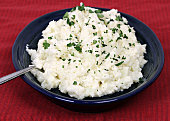 Mashed cauliflower, a popular replacement for potatoes, on a blue dish garnished with fresh parsley snips.