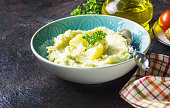 Mashed cauliflower with oil in blue bowl on wooden table. Dinner for a low-carb, keto diet