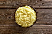Mashed potatoes in bowl on wooden background. Top view, flat lay