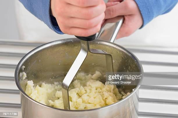 Mashing potato in a pan, close up