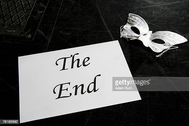 A mask and a sign for 'The End' on a theater stage