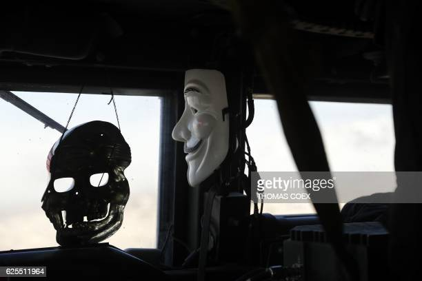 A mask of Guy Fawkes and another of a skull hang inside an Iraqi Special Forces armoured vehicle as they advance in a district of Northeastern Mosul...