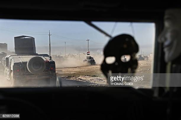 TOPSHOT A mask of Guy Fawkes and another of a skull hang inside an Iraqi Special Forces armoured vehicle as army vehicles advance in a district of...