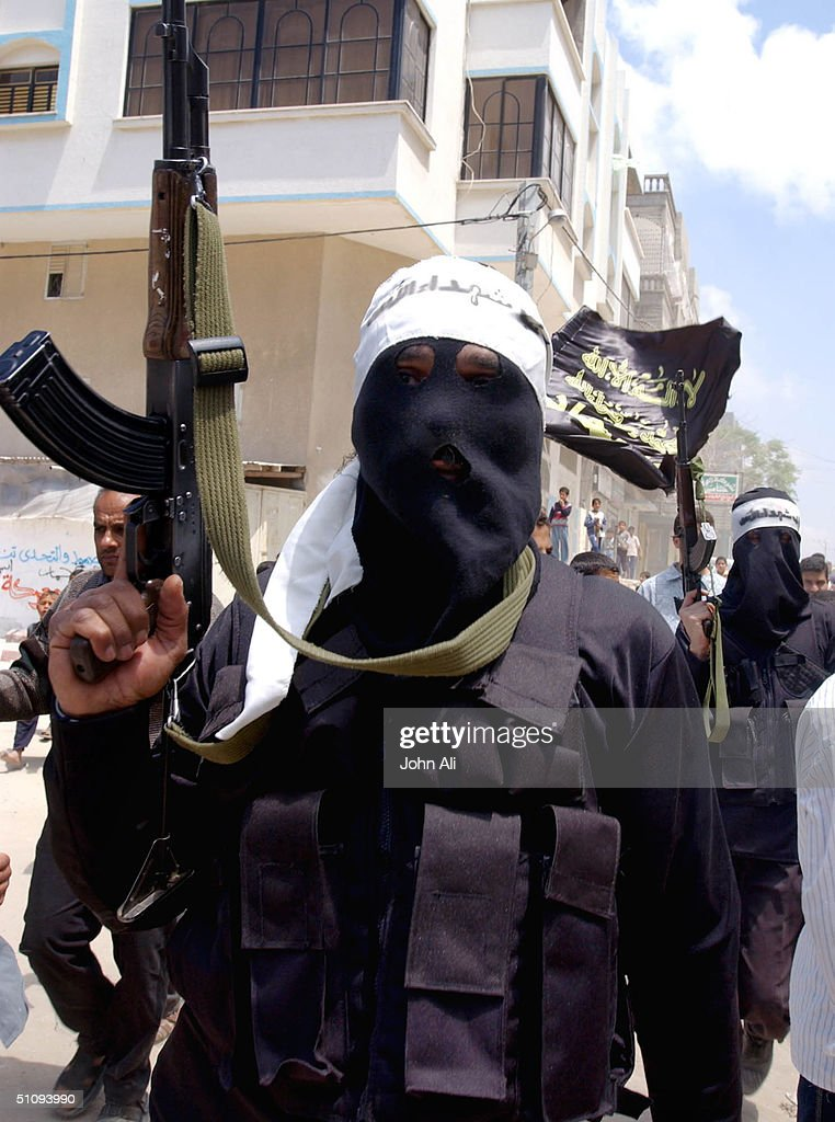 Masked Activists Of The Al Aqsa Martyrs' Brigade A Militia Linked To Palestinian Leader Yasser Arafat's Fatah Movement Brandish Weapons As They March...
